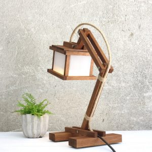 Create ambiance in a workspace of your choice with the Kran Paus Wooden Desk Lamp. This eye-catching piece of work holds an inspiring and creative style that would suit any professional environment.